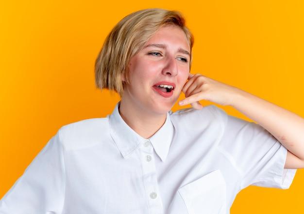若い泣いている金髪のロシアの女の子のジェスチャーは、コピースペースでオレンジ色の背景に分離されたサインを呼び出す
