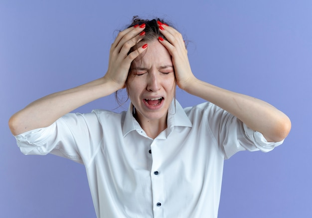 若い泣いている金髪のロシアの女の子は、コピースペースで紫に頭を抱えています