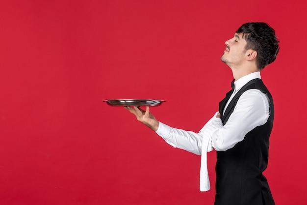 Giovane uomo curioso cameriere in uniforme con farfalla sul collo che tiene vassoio e asciugamano su sfondo rosso