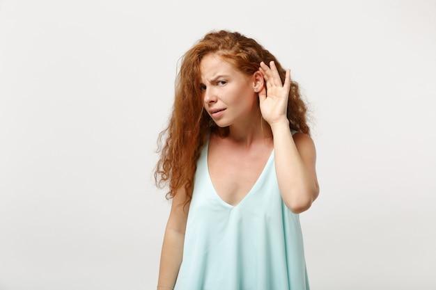 白い壁の背景に分離されたポーズのカジュアルな明るい服を着た若い好奇心が強い赤毛の女性の女の子。人々の誠実な感情のライフスタイルの概念。コピースペースをモックアップします。耳の近くの手であなたの声を聞いてみてください。