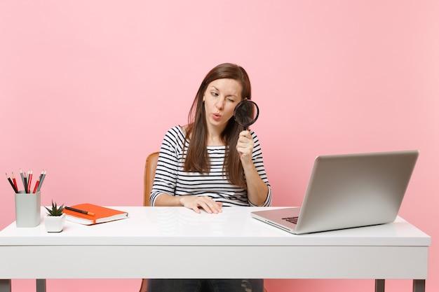 젊은 호기심 많은 여성은 파스텔 핑크색 배경에서 격리된 사무실에서 프로젝트에 앉아 일하는 동안 pc 노트북의 돋보기를 통해 자세히 살펴봅니다. 성취 비즈니스 경력 개념입니다. 공간을 복사합니다.