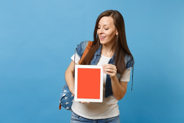 Young curious woman student with backpack holding and looking on tablet pc computer with blank black empty screen isolated on blue background. education in high school. copy space for advertisement.