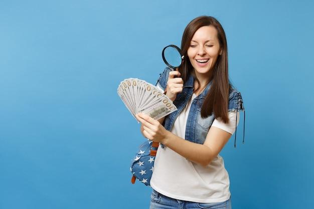 배낭을 메고 있는 호기심 많은 여학생은 많은 달러, 파란색 배경에 격리된 돋보기 수표 지폐가 있는 현금 돈을 봅니다. 돈 개념의 진위 여부를 확인합니다.