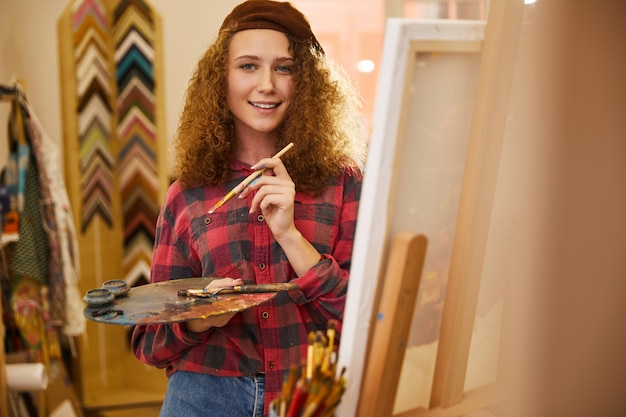 Young curly artist looks happy and holds a palette with oil paints