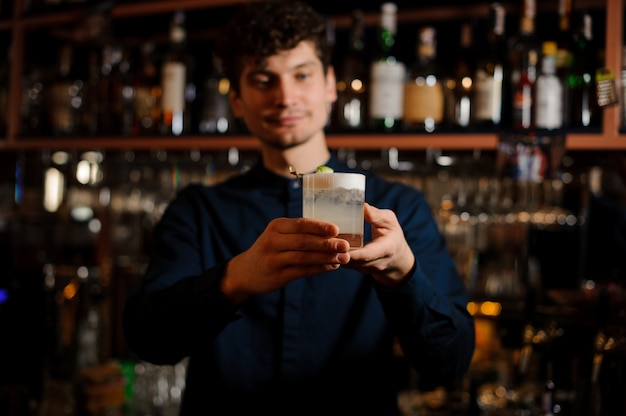 Young curly barman holding a glass with fresh and sour summer cocktail