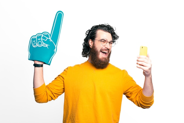 Young curly bearded man is excited about new on the phone, points up with his fan glove.