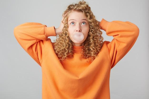 Молодая кудрявая блондинка, одетая в ярко-оранжевый свитер большого размера, стоит с руками возле головы