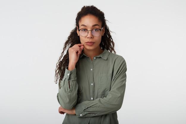 Giovane donna dalla pelle scura bruna riccia in occhiali alzando la mano al viso e guardando pensieroso, in piedi su bianco