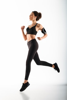 Young curly brunette fitness woman running and listening music