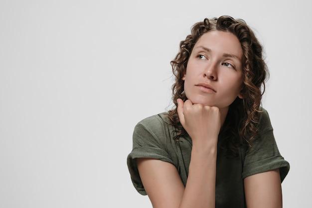 Молодая кудрявая кавказская женщина держит руку под подбородком, задумавшись, о чем-то думает