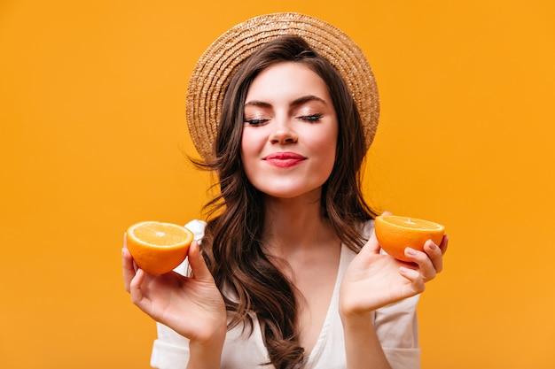 Молодая кудрявая темноволосая женщина в канотье держит апельсины и позирует с закрытыми глазами.