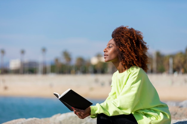 Young curly fro woman sitting on a breakwater holding a book while smiling and looking away outdoors