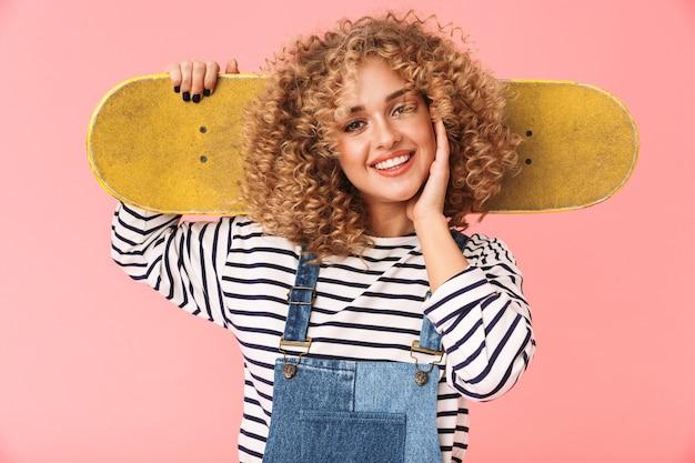 서있는 동안 스케이트 보드를 들고 젊은 곱슬 소녀 20 대