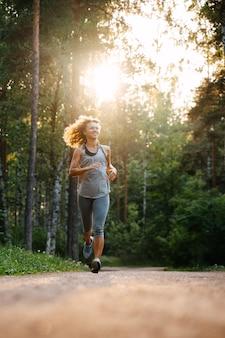 Молодая кудрявая девушка весело пробегает марафон по лесной дороге на рассвете здорового образа жизни