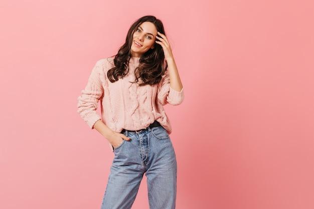 Молодая кудрявая девушка позирует с белоснежной улыбкой на розовом фоне. женщина в джинсах мамы смотрит на камеру.