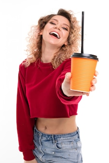 Young curly girl with a smile on her face holds a glass of coffee on outstretched hand