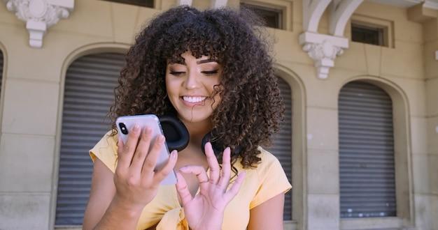 携帯電話を使用して歩いている若い巻き毛の黒人女性。路上でのテキストメッセージ。大都市。