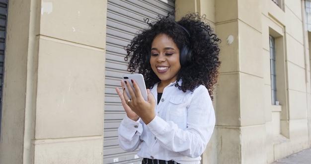 Молодая чернокожая женщина вьющихся волос, идущая с помощью мобильного телефона текстовые сообщения на улице. большой город.