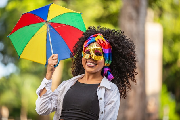 Young curly hair woman celebrating the brazilian carnival party with frevo umbrella on street.