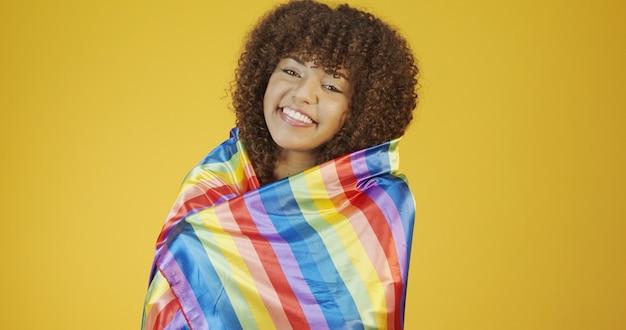 Lgbtプライドフラグで覆っている若い巻き毛の女性。 1人。一。 lgbtの旗をかぶって、こぶしを上げ続けます。黄色の背景にlgbt +フラグ。