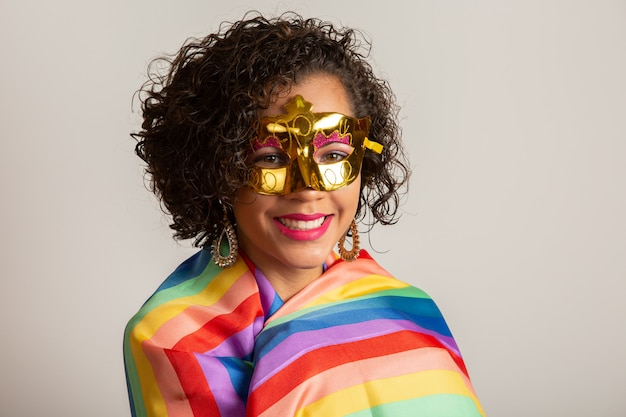 Lgbtプライドフラグでカバーするカーニバルパーティーを楽しんでいる衣装の若い巻き毛の女性。一人で。 1。拳を上げて、lgbtフラグをカバーします。白い背景のlgbt +フラグ。