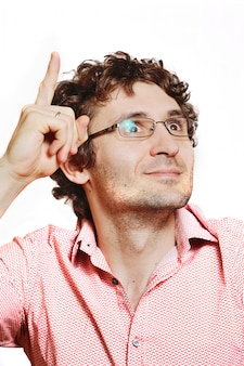 Young curly-haired guy is thinking on a white background