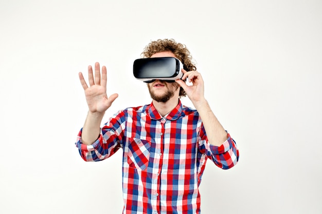 Young curly-haired man in plaid shirt using a vr headset and exp