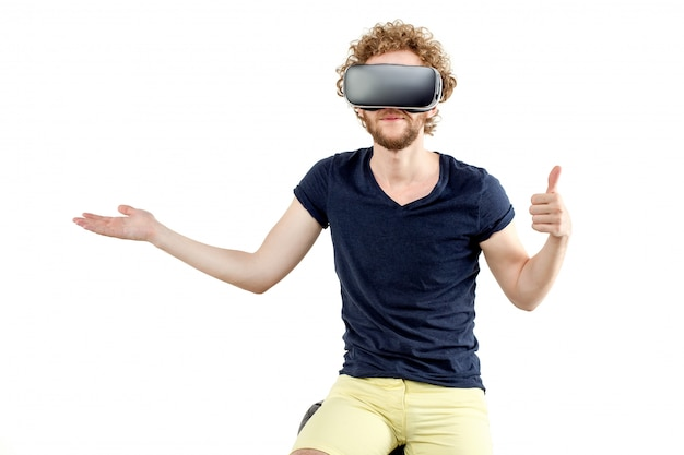 Young curly-haired man using a vr headset and experiencing virtu