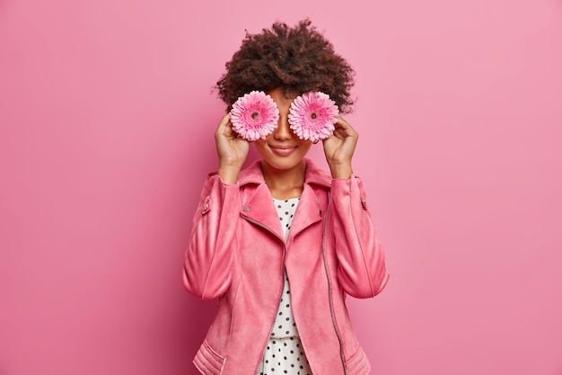 Young curly haired woman holds pink gerbera daisy flower, covers eyes, dressed in fashionable pink jacket, makes decoration, poses indoor.