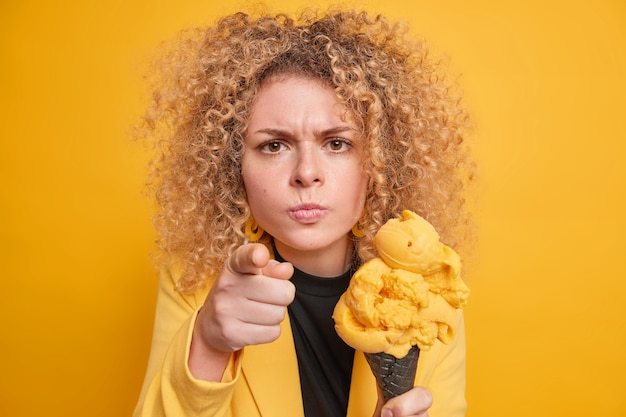 Young curly haired woman looks angrily and points directly  blames you holds delicious ice cream eats yummy summer dessert dressed in formal clothes isolated over yellow wall.
