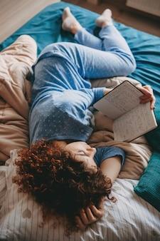 Молодая кудрявая женщина читает книгу в постели в пижаме