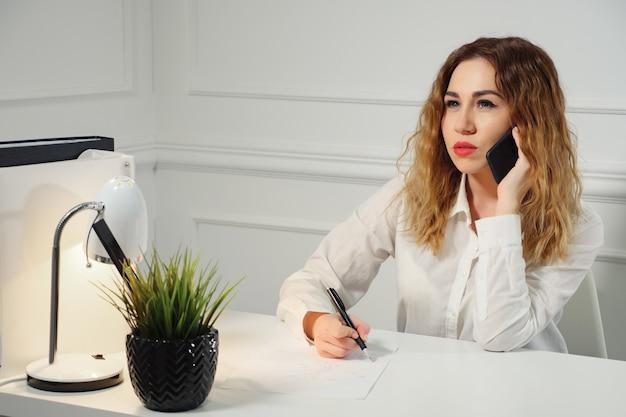 Молодая кудрявая женщина-секретарь разговаривает по мобильному телефону с клиентом и делает заметки, сидя за столом в офисе. концепция работы офиса.