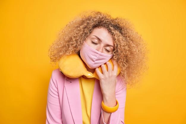 若い縮れ毛の女性は首の枕で寝て目を閉じたままにします