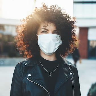 晴れた日にカメラでポーズをとって外で医療マスクを身に着けている若い巻き毛の髪の女性