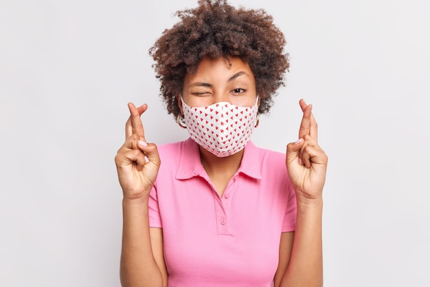 Young curly haired woman wears protective face mask crosses finger believes in dream come true hopes not to catch coronavirus dressed in pink t shirt isolated over white wall