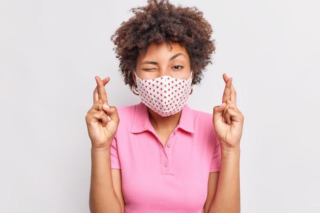 Молодая кудрявая женщина в защитной маске пересекает палец, верит в сбывшуюся мечту, надеется не заразиться коронавирусом, одетая в розовую футболку, изолированную над белой стеной