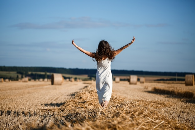 Young curly-haired woman in a wheat field, where there is a huge sheaf of hay, enjoying nature. people and travel. nature. sun rays agriculture