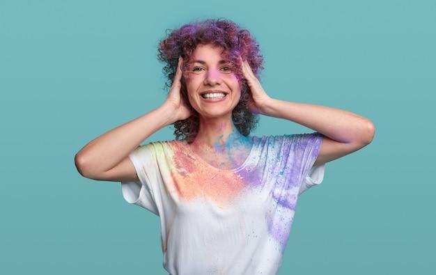 パーティーを楽しむホーリー色の若い巻き毛の髪の女性