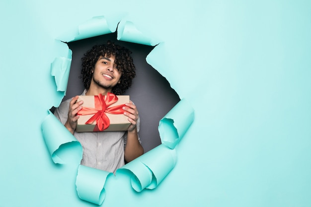 Young curly handsome man holding gift from hole on green paper
