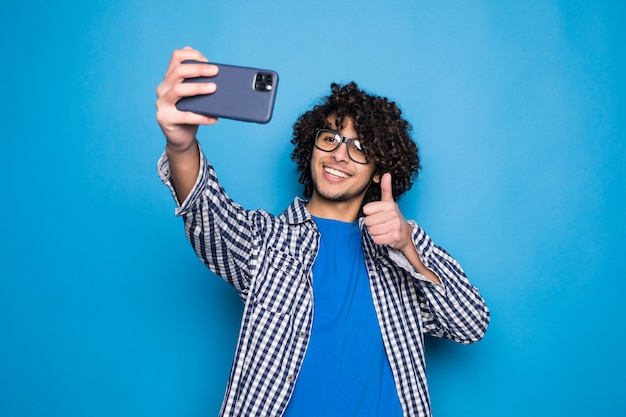 Giovane uomo bello riccio che fa un selfie sopra la parete blu isolata