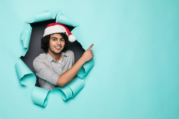 Young curly handsome man wear in santa hat pointed side from hole on green paper