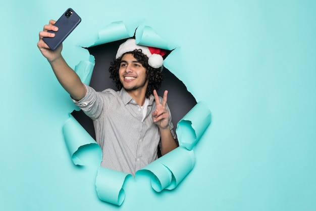 Young curly handsome man wear in santa hat take selfie from hole on green paper