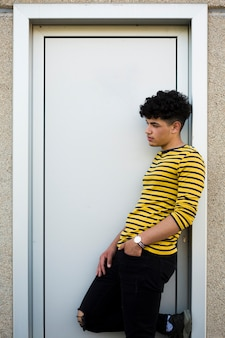 Young curly hispanic man leaning on door casing