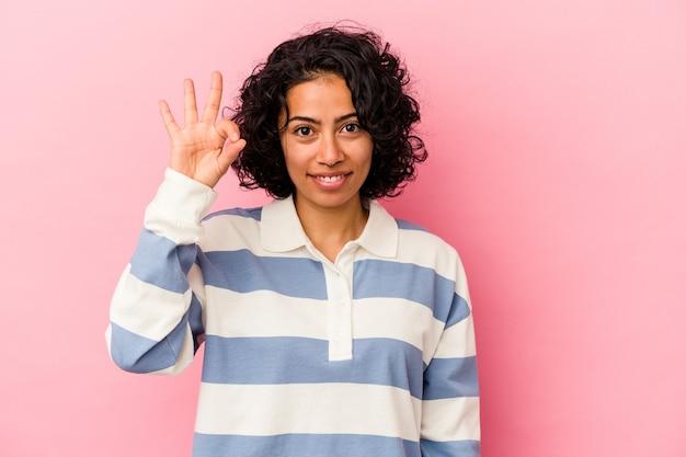 ピンクの背景に分離された若い巻き毛のラテン女性は、明るく自信を持って大丈夫なジェスチャーを示しています。