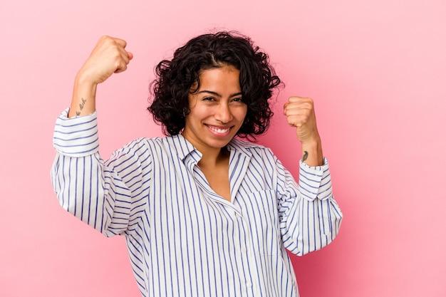 のんびりと興奮して応援ピンクの背景に分離された若い巻き毛のラテン女性。勝利の概念。