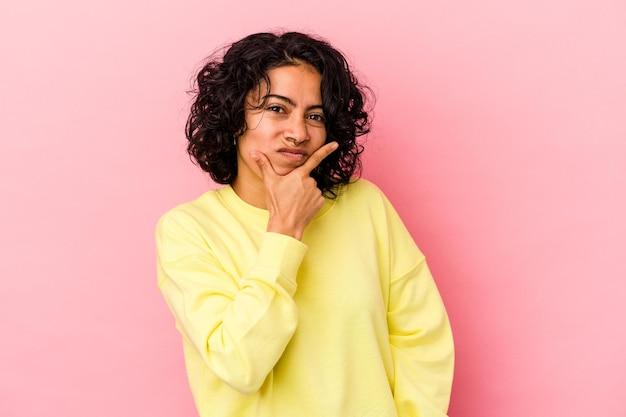 ピンクの背景に孤立した若い巻き毛のラテン女性は、ビジネスの方法を考え、戦略を計画し、考えています。