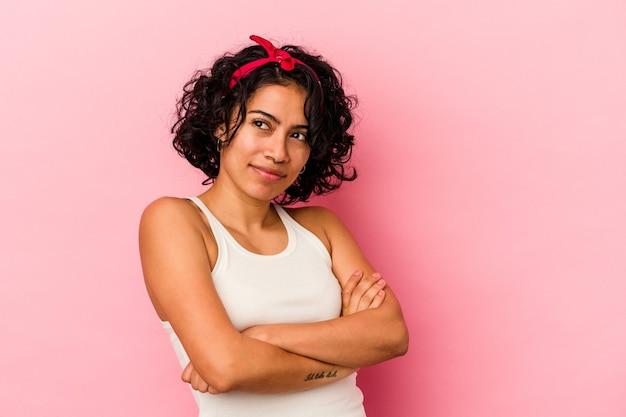 目標と目的を達成することを夢見てピンクの背景に分離された若い巻き毛のラテン女性