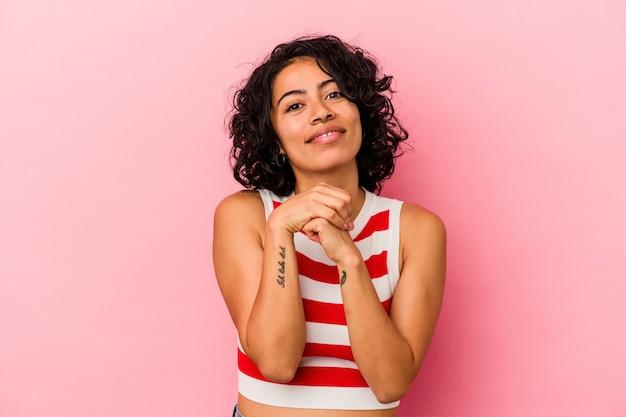 Молодая фигурная латинская женщина, изолированная на розовом фоне, держит руки под подбородком, счастливо смотрит в сторону.