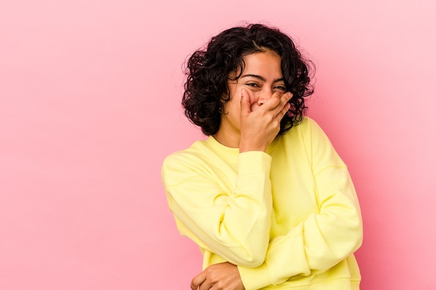 幸せな、のんき、自然な感情を笑ってピンクの背景に分離された若い巻き毛ラテン女性。