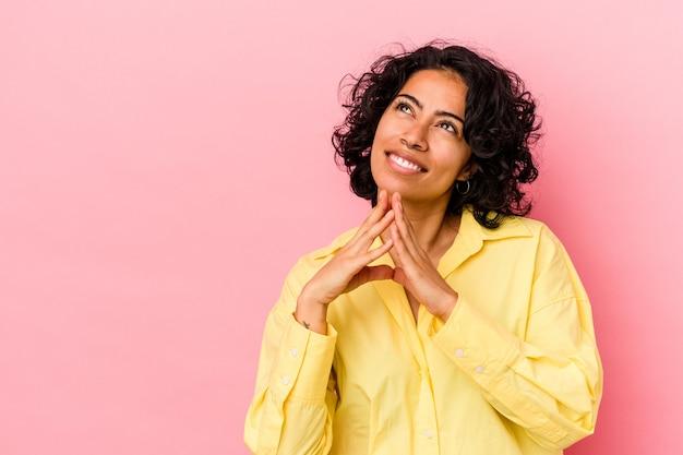 ピンクの背景に若い巻き毛のラテン女性が計画を立て、アイデアを設定する。